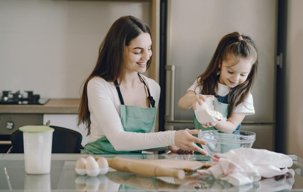 Girl pouring flour in bowl with mother