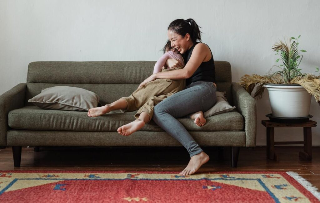 Mother sitting on couch, laughing and hugging her child