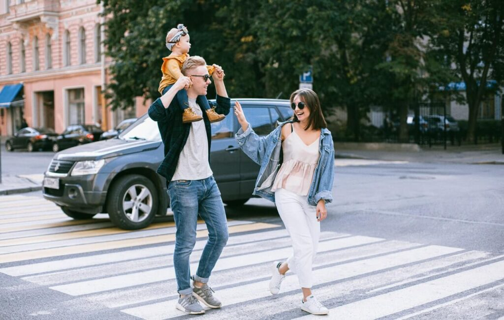 Family laughing and walking on a pedestrian lane
