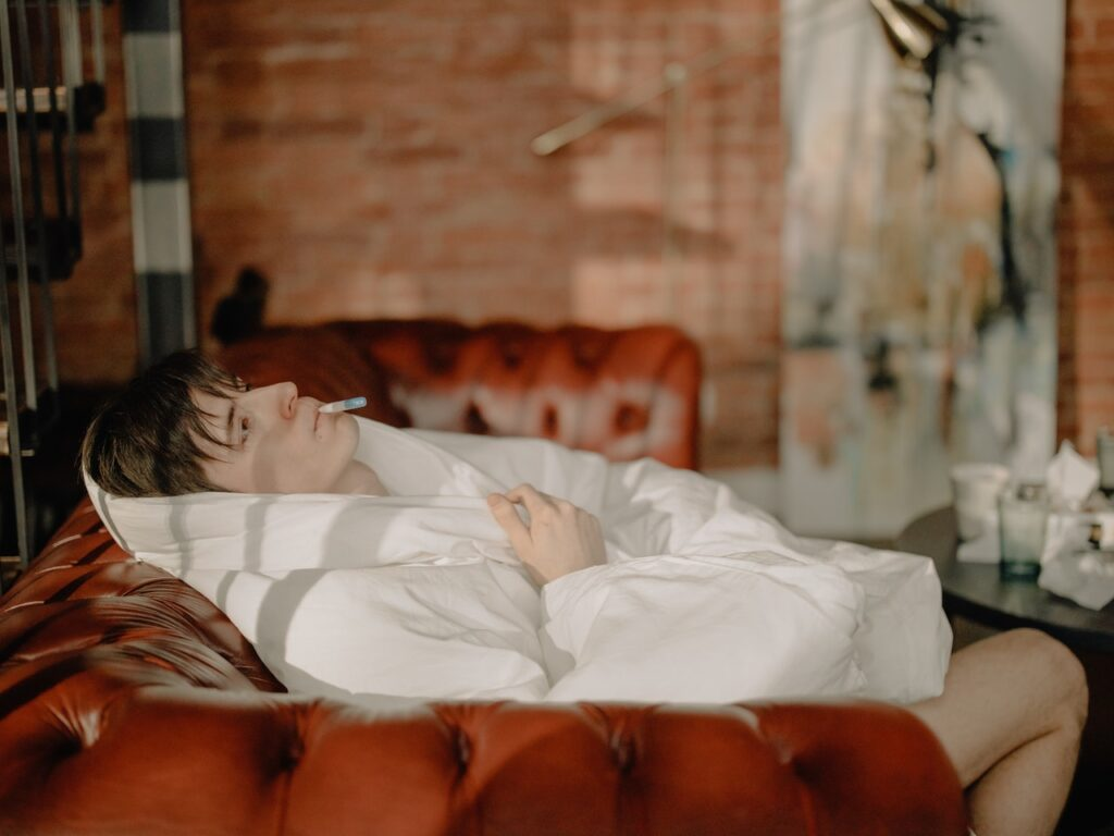 A sick person lying on bed covered with white blanket