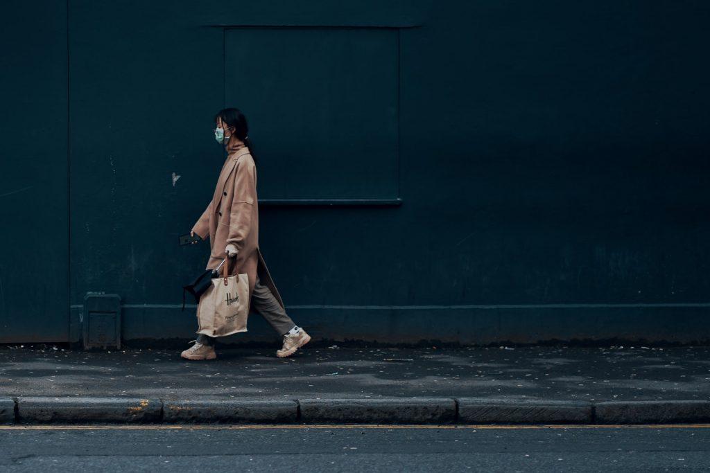 woman walking on footpath wearing mask