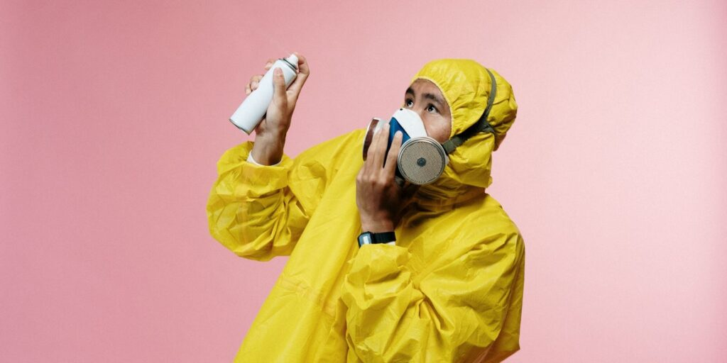 Adult wearing Coronavirus gear and disinfecting in fear