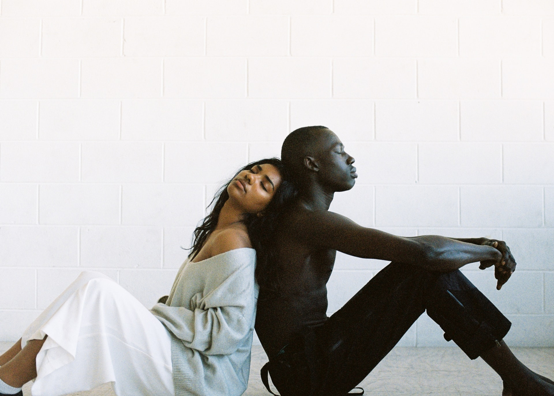 Black man and woman sitting back to back feeling depressed