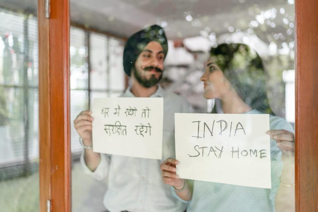 Couple holding display cards with message to Stay at Home