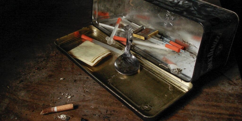 A tin box with drugs, syringes, and substance