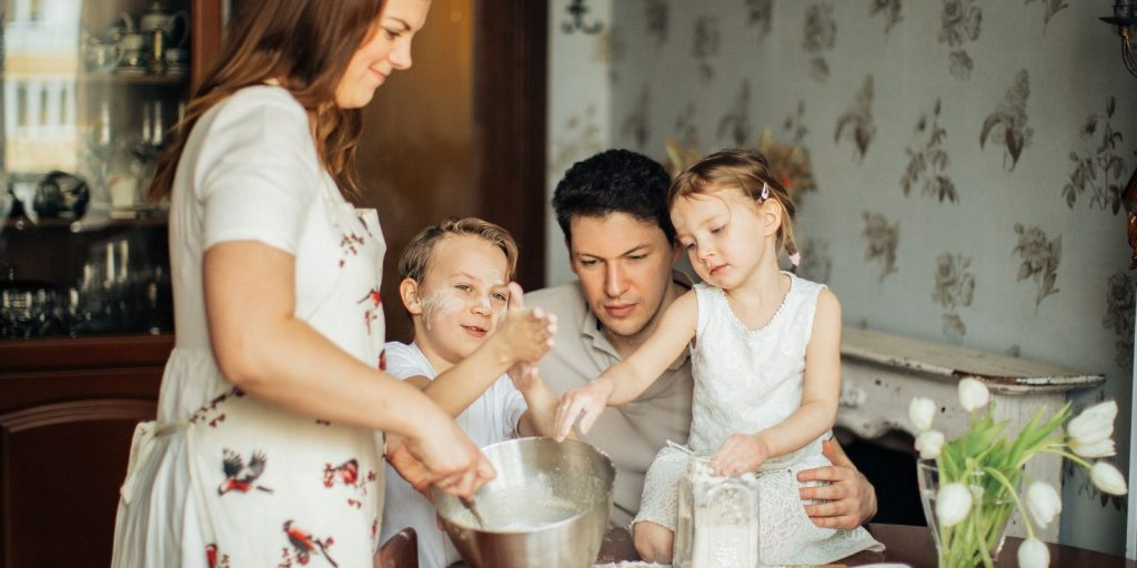 Family photo with children and parents mixing ingredients