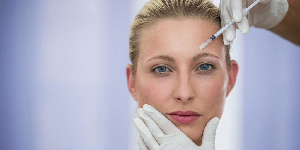 Image of a woman receiving Botox injection by a dermatologist