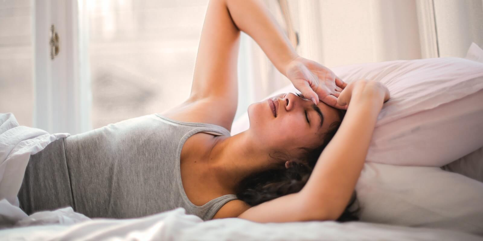 Woman in grey tank top lying in bed having headache and body pain