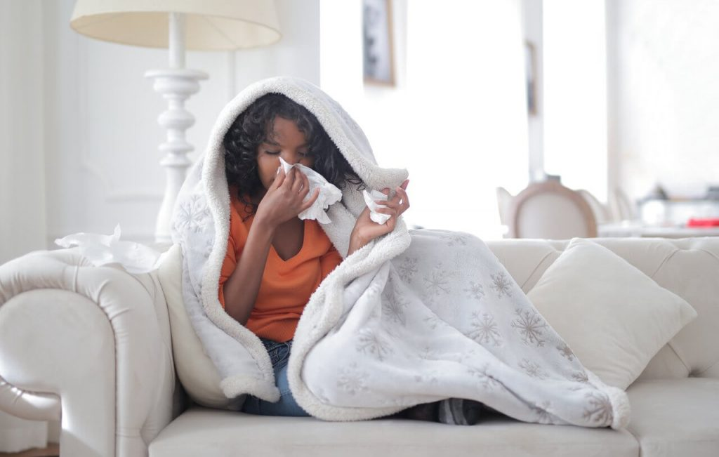 Image of a young ethnic woman sitting on sofa having coronavirus symptoms of flu and body chills
