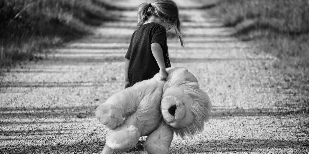 Image of sad Child walking on road holding a teddy bear