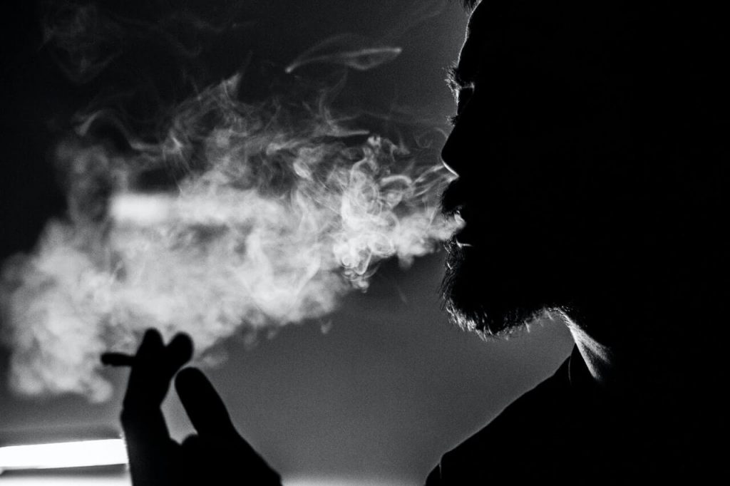 Man holding cigarette and smoking