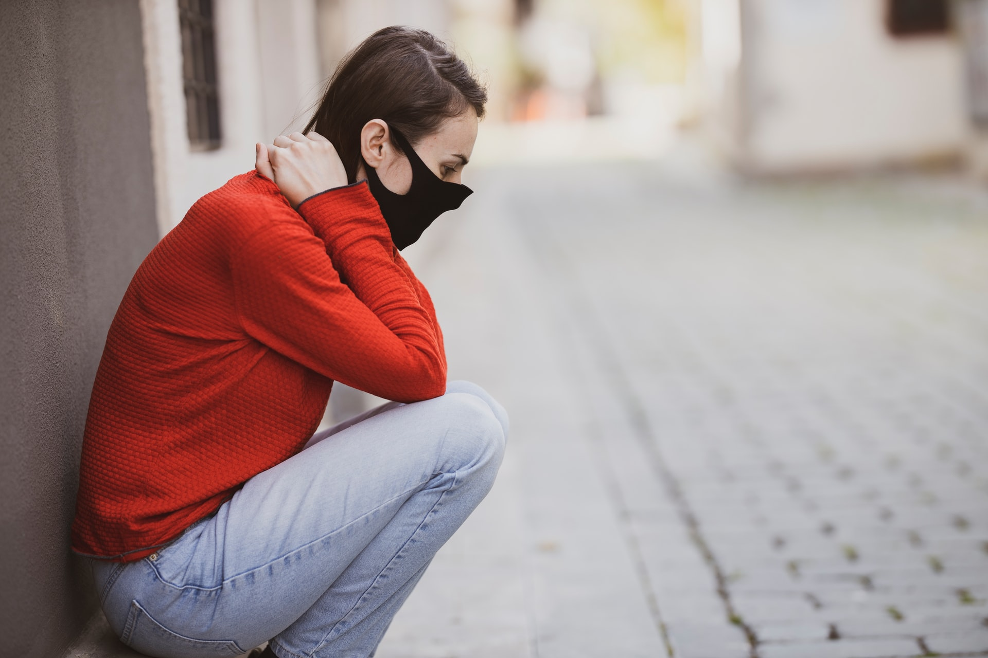 Woman sitting on a footpath feeling distressed