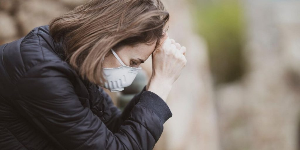 Image of a woman feeling fatigue and wearing mask
