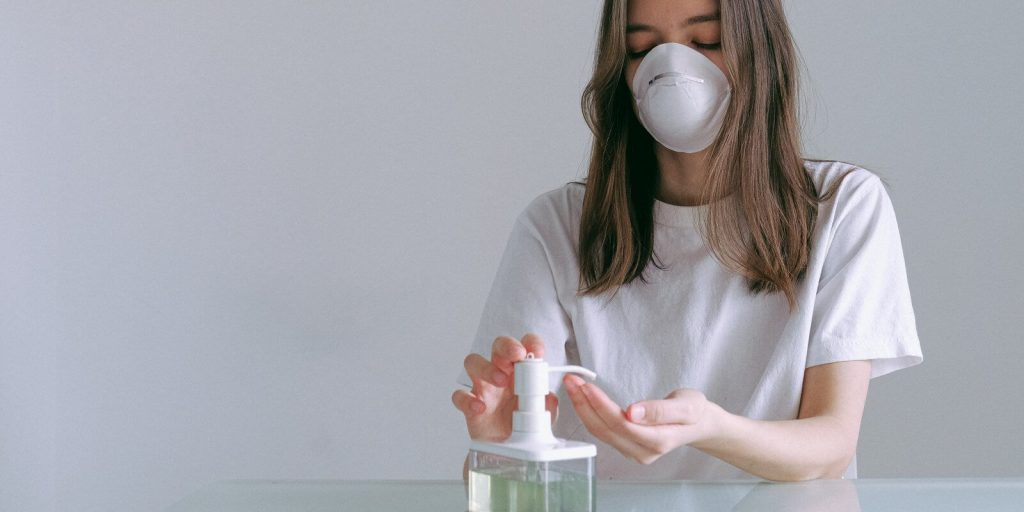 Image of a woman in white shirt, wearing a masks and using hand sanitizer