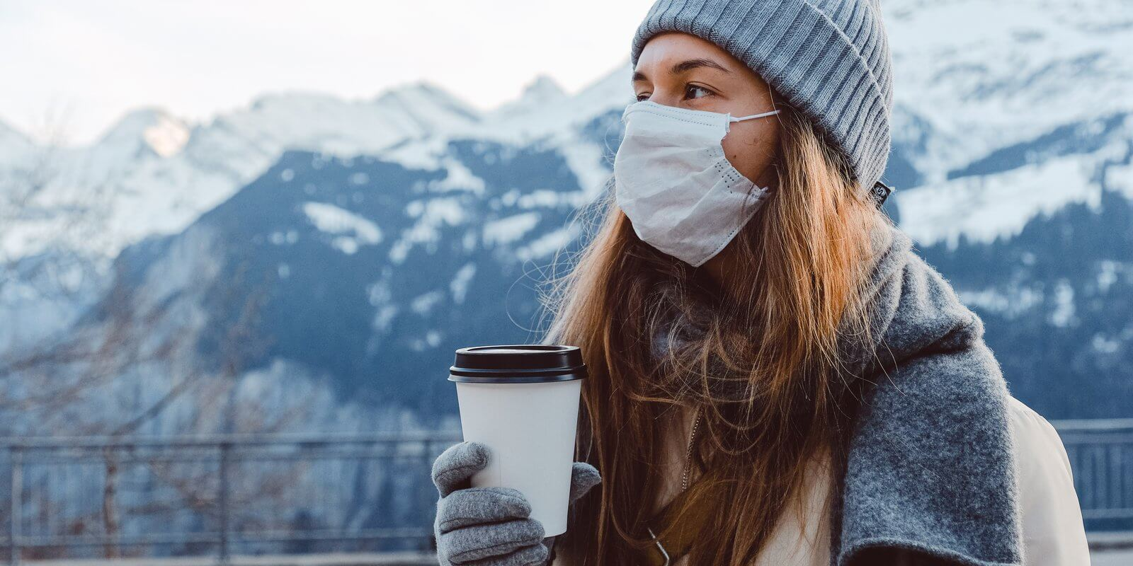 Image of a Woman wearing warm clothes and mask in winters holding a coffee cup