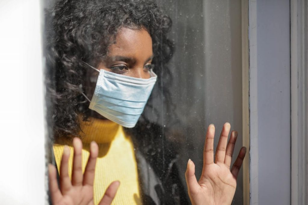 A serious young ethnic woman at home wearing medical mask
