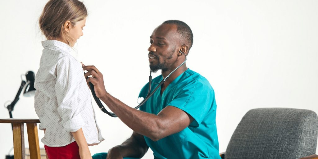 Doctor examining a teenage girl with stethoscope