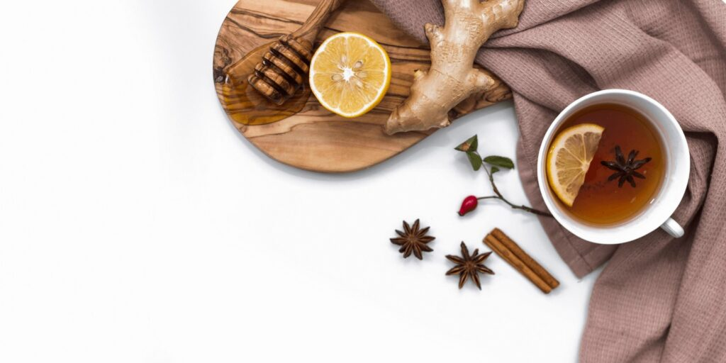 Ginger tea with ginger root, lemon, and honey with a brown cloth on white background