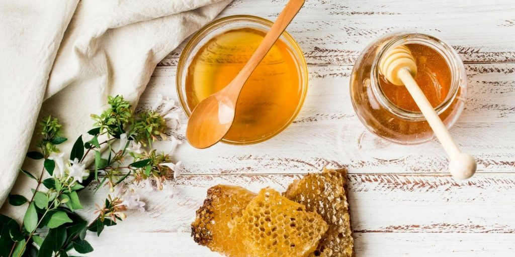Image of Honey jar with honeycomb on a solid surface with herbs