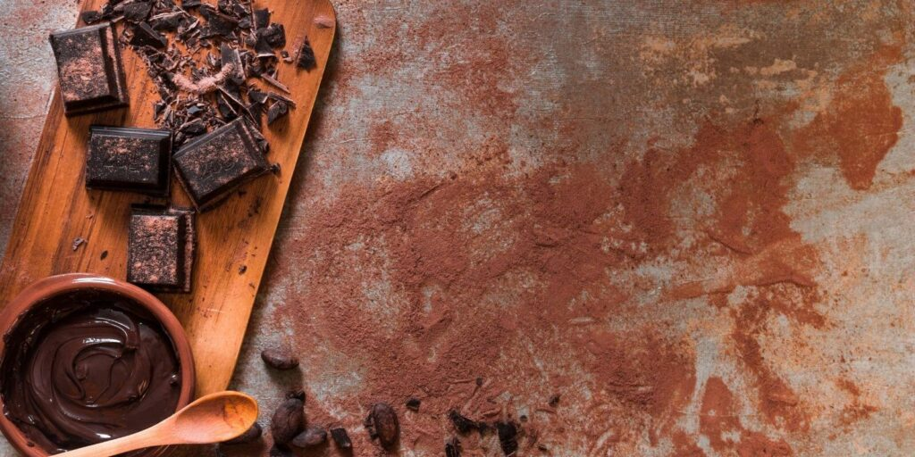 Melted and crushed dark chocolate chunk on a cutting board