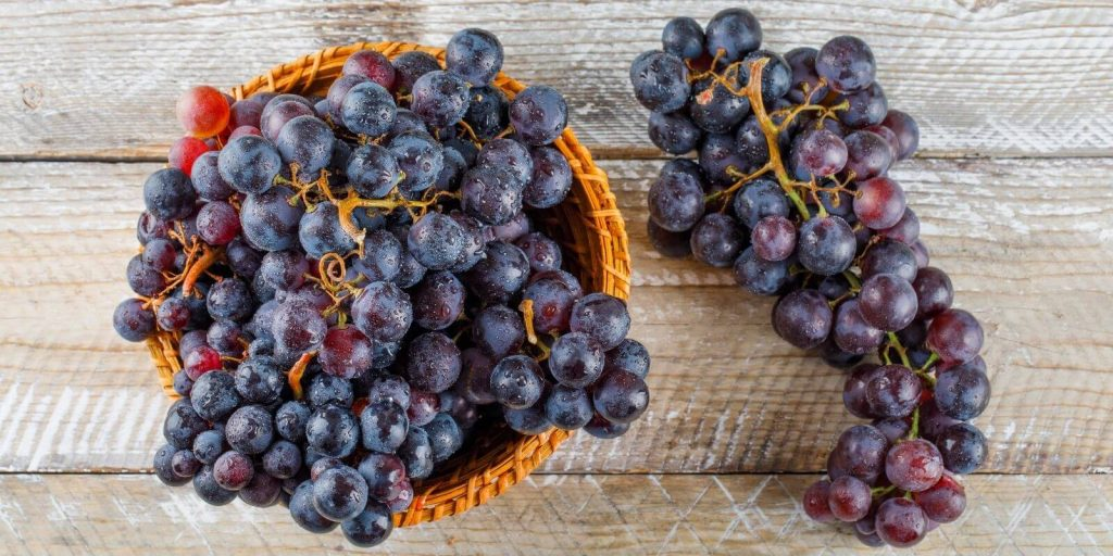 Purple grapes in basket on a wooden background