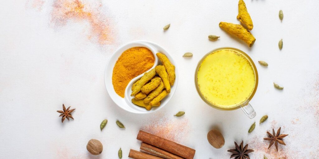 Turmeric powder and turmeric milk paste on a marble background