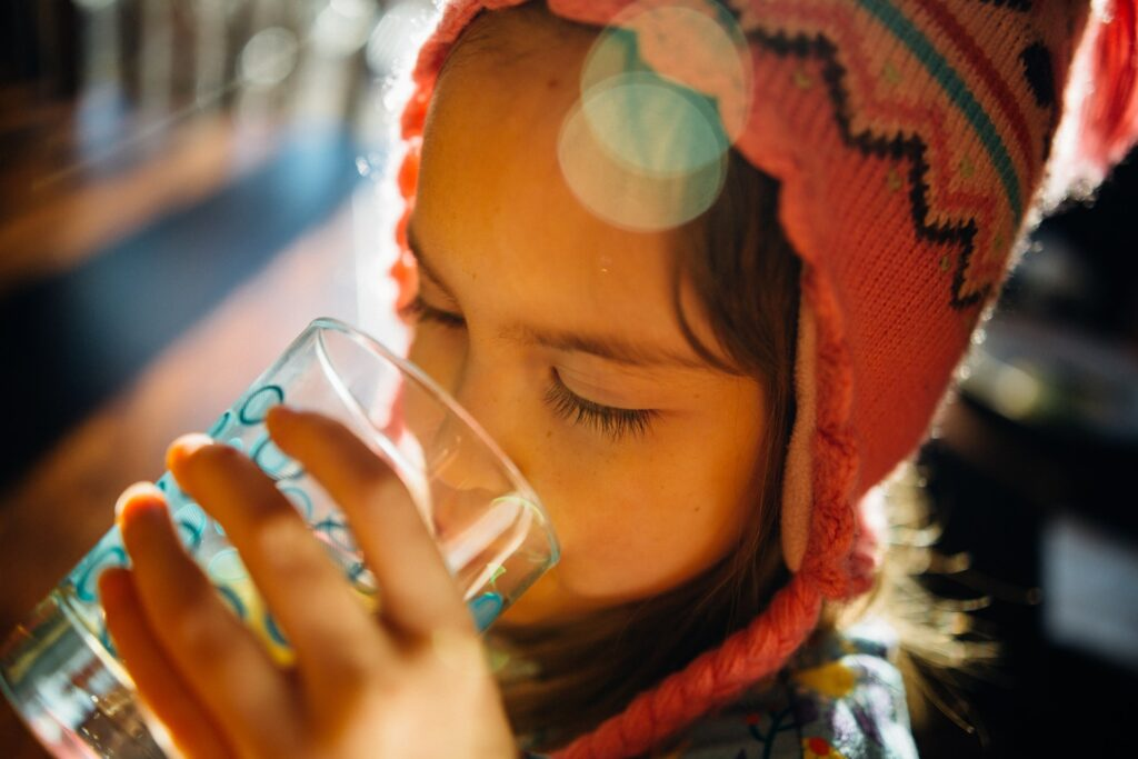 A little girl drinking water from a glass