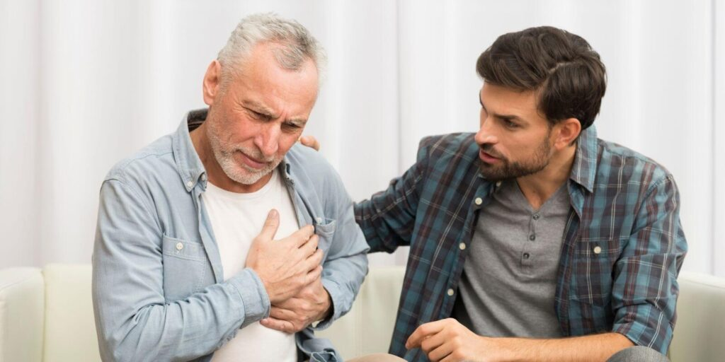 Old man experiencing chest pain and muscle tension sitting besides a young man