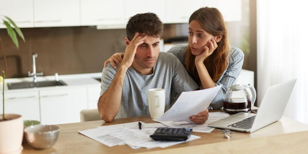 Young couple feeling stressed checking the family budget