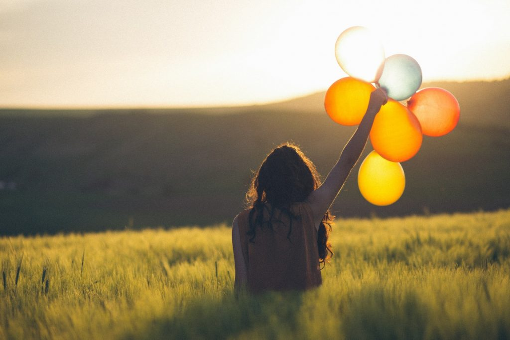 A happy person with baloons in the green valley